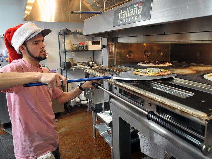 Josh Holcomb pulls a fresh pizza from an Italian-made