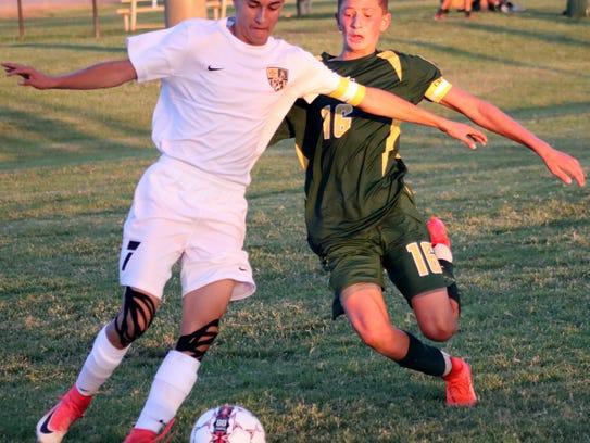 Alamogordo's Keith Wilder, left, advances the ball