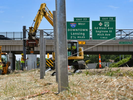 Workers construct cable barriers in the US-127 median