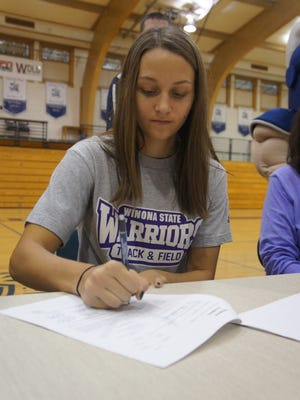 Columbus Catholic senior Alexandra Hutchison signs her national letter of intent to compete for Winona State in track on Wednesday.