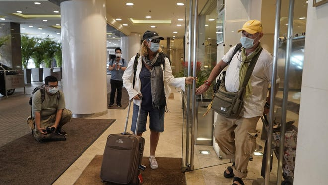 Hotel guests wearing face masks, leave the Royal Garden Hotel in Hong Kong, Friday, Oct. 9, 2020. The Royal Garden Hotel was evacuating all of its guests after the government confirmed that a waiter who worked at a Vietnamese restaurant at the hotel was found to have the coronavirus COVID-19.