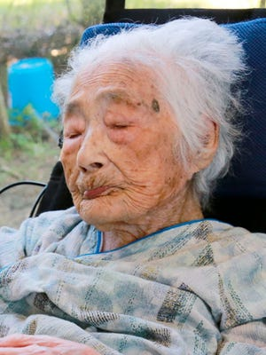 This Sept. 2015 photo shows Nabi Tajima, the world's oldest person, a 117-year-old Japanese woman. Tajima died of old age, at 117, in a hospital Saturday evening, April 21, 2018, in the town of Kikai in southern Japan, town official Susumu Yoshiyuki confirmed. She had been hospitalized since January.