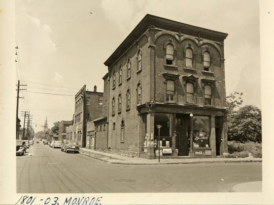This is a historical photo of Black Bottom before it was torn down in the 1950s to make way for the Chrysler Freeway and the Detroit Medical Center. In this photo a building sits on the corner at 1801 and 1803 Monroe St. on August 26, 1949 in Black Bottom, the ancestral neighborhood of many metro Detroit African Americans.