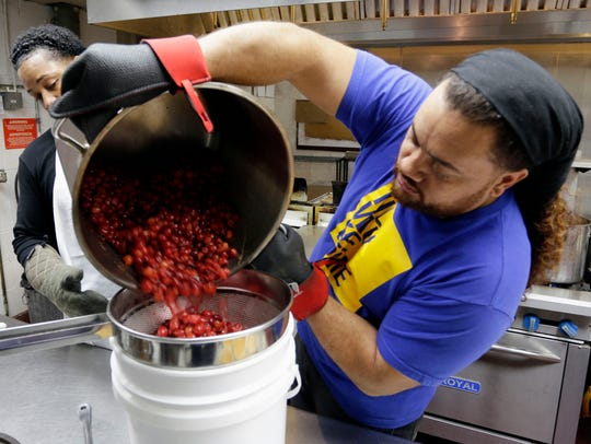 Johnathan Dye strains cherries for use in one of his specialty pies at Mr. Dye's Pies Feb. 2, 2017, in Milwaukee.