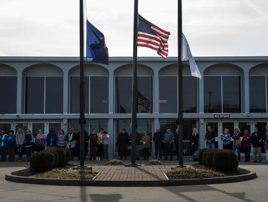 Members of the community gather around the half-staff