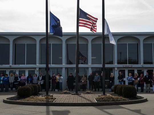 Members of the community gather around the half-staff flags for prayer outside Henderson County High School on Sunday, Feb. 18, 2018. Community church members gathered at the high school after Sunday services to pray for the safety of students.