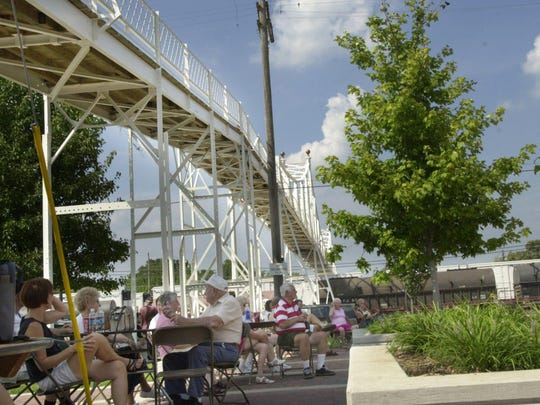 People gather under the newly restored Jefferson Avenue Footbridge to enjoy sunshine, music and join the centennial celebration for the bridge on Monday afternoon.