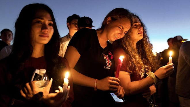 People attend a candlelit memorial service for the victims of the shooting at Marjory Stoneman Douglas High School that killed 17 people on Thursday, February 15, 2018 in Parkland, Florida. The shooting prompted a Florida 'red-flag' law that allows the courts to limit temporarily a person's access to guns if they're deemed a threat to themselves or others.