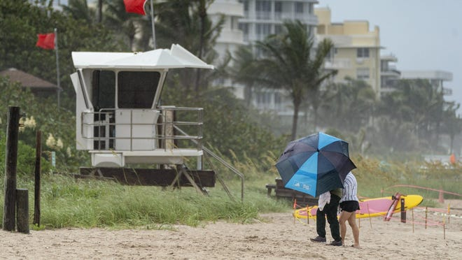 A couple under an umbrella leave the beach as it starts raining again in Lake Worth Beach, Florida on May 25, 2020.