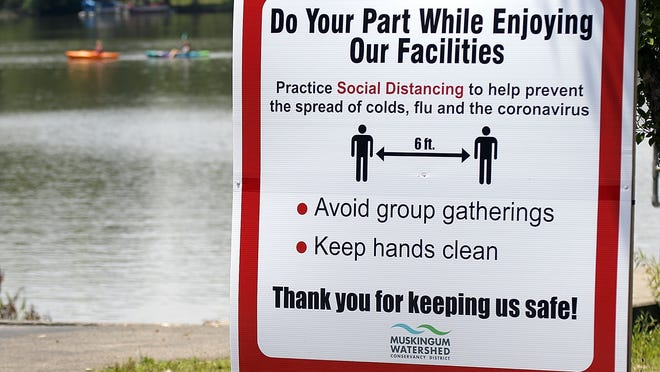 A sign is posted at the Charles Mill Lake boat launch ramp off Ohio 430 reminding guests to practice social distancing while using the facilities as two kayakers head out on Charles Mill Lake on Wednesday.