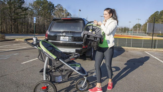 Lindsey Caballero places son, Colton, into his stroller as she prepares to lead a Stroller Strong Moms exercise class in Marietta, Ga. The stroller-based boot camp offers a unique opportunity for women to exercise with their children and fellow mothers.
