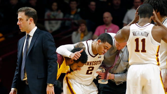 Minnesota head coach Richard Pitino, left, heads to the bench to as Nate Mason, center, is attended to after being injured in the second half of an NCAA college basketball game against Florida Atlantic Saturday, Dec. 23, 2017, in Minneapolis. (AP Photo/Jim Mone)