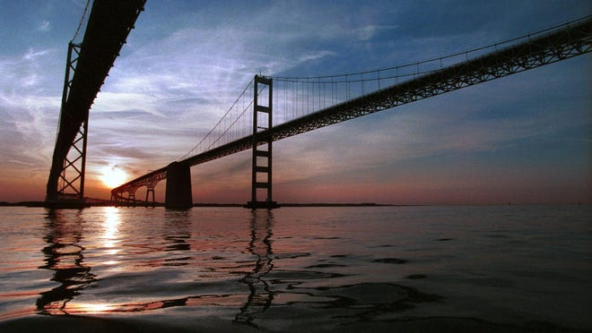 The twin spans of the Bay Bridge reflect into the Chesapeake at sunset.