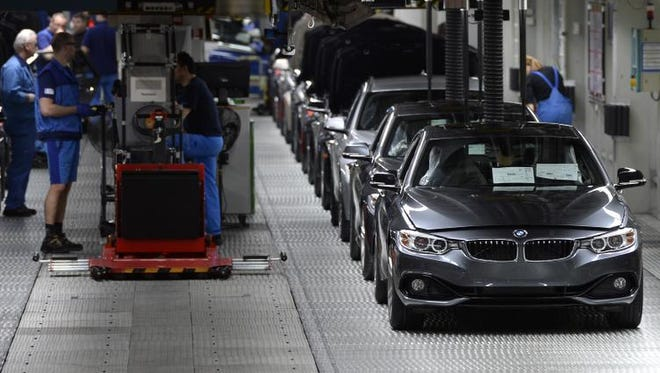 Employees of German car maker BMW work on an assembly line for BMW cars at the company's plant in Munich, southern Germany, on March 18, 2014.