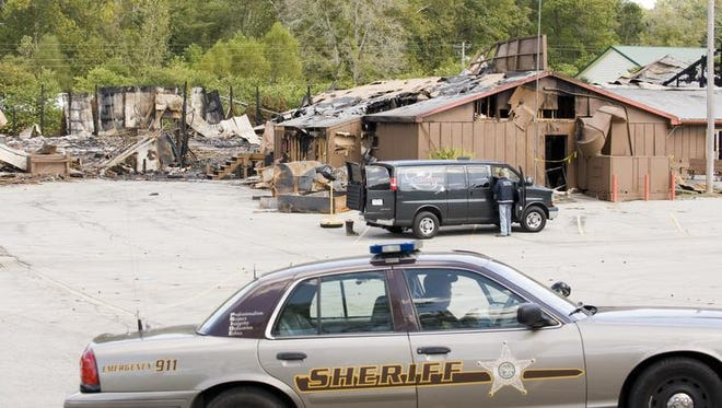 A Brown County Sheriff's Department deputy watches over the fire scene at the destroyed Little Nashville Opry on Sept. 28, 2009, near Nashville, Ind.