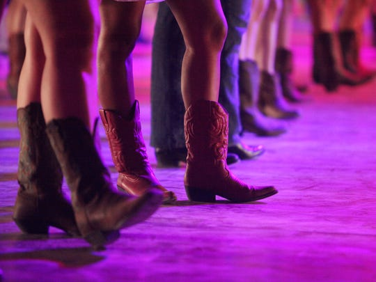 Country music fans take part in a line dance lesson at the Honky Tonk Dance Hall during Stagecoach on Friday, April 25, 2014 in Indio, Calif.