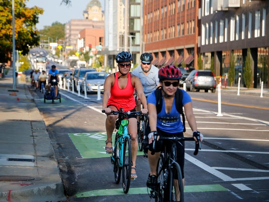 Cyclists ride the protected bike lanes on East Grand Avenue in Des Moines on Sept. 11, 2017.