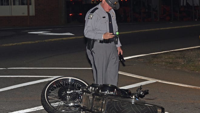 A South Highway Patrol trooper stands near a motorcycle that crashed into an ambulance Friday evening in Anderson County.