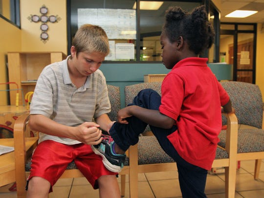 Austin, 13, ties Cassy's shoe in the lobby of the Salvation Army as they wait to get into the sanctuary where the family sleeps.