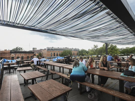 People gather on Illegal Pete's deck patio in Old Town Fort Collins on July 15, 2015.