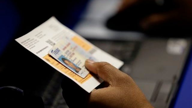 In this Feb. 26, 2014 file photo, an election official checks a voter's photo identification at an early voting polling site in Austin, Texas. (AP Photo/Eric Gay, File)
