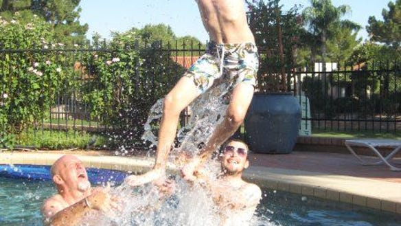 Jamie Showkeir and Chris Aguirre toss Sawyer into the air at a Fourth of July gathering.