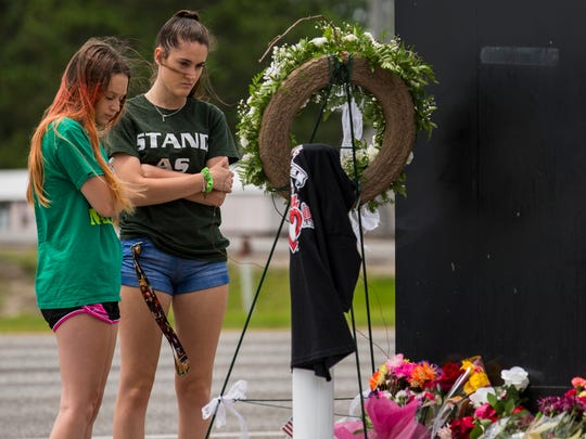 Kalysta Dodson, left, and Reagyn Murphy, sophomores at Santa Fe High School, look at a memorial for the victims of the Santa Fe High School.