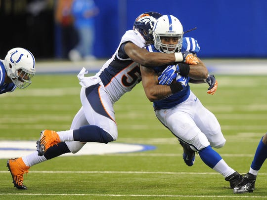 Indianapolis Colts' Trent Richardson (34) is wrapped up by Denver Broncos' Danny Trevathan (59) in 2013.