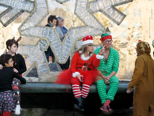 Leah Crisp and David Skinner sit on the fountain at Pack Square December 2 for SantaCon 2017.