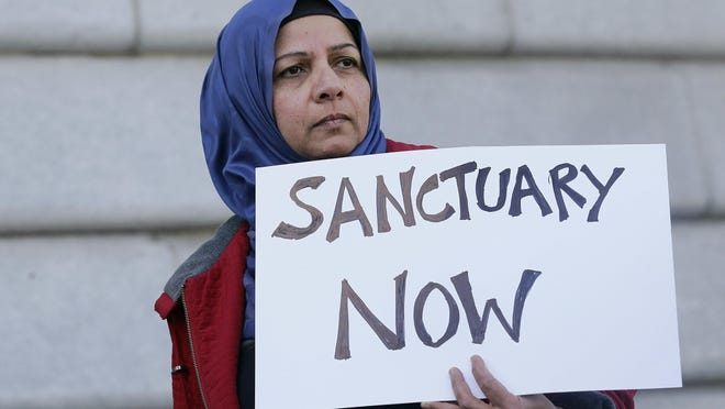 In this Jan. 25, 2017 file photo, a woman holds a sign at a rally outside of City Hall in San Francisco. The Trump administration is moving beyond rhetoric in its effort to crack down on so-called sanctuary cities that refuse to cooperate with federal immigration authorities.