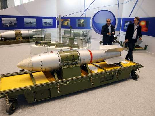 Visitors walk near a mock Soviet RN-28 Compact bomb