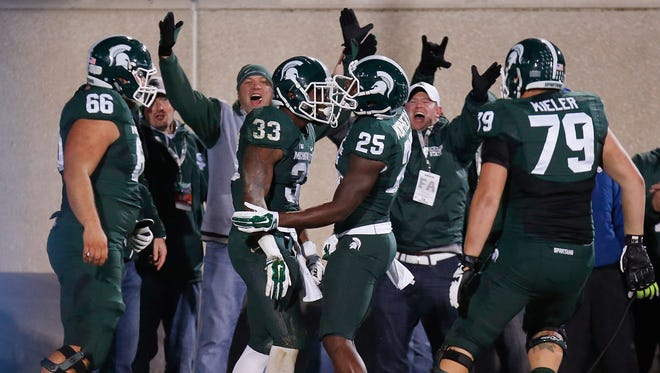 Jeremy Langford #33 of the Michigan State Spartans celebrators a first-quarter touchdown with Keith Mumphery #25, Kodi Kieler #79 and Jack Allen #66 against the Nebraska Cornhuskers at Spartan Stadium on October 4, 2014 in East Lansing, Michigan.
