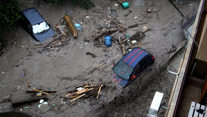 Cars are covered in mud in the flooded area of the Black sea town of Varna, Bulgaria, Thursday, June 19, 2014. Two people and a child are reported dead and four more are missing. Torrential rain caused severe flooding in Bulgaria, sweeping away cars, reducing scores of homes to rubble, the country's civil defense authority said.