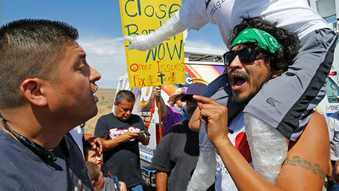 Sergio Garcia of San Diego and Osvaldo Delgado of El Paso, Texas, argue during a immigration demonstration outside the Border Patrol facility July 4, 2014 in Murrieta, Calif.