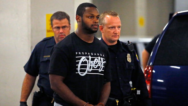 Phoenix police officers escort Arizona Cardinals running back Jonathan Dwyer to the 4th Avenue Jail following his arrest on suspicion of aggravated assault  Wednesday, Sept. 17,  2014 in Phoenix, Arizona.
