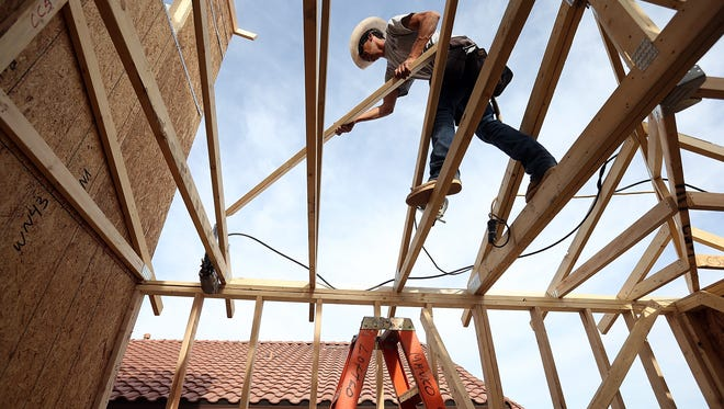 A worker builds a new home at the Pulte Homes Fireside at Norterra-Skyline housing development in Phoenix.