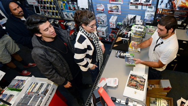 Store manager Brandon Khan, right, sells copies of 'Call of Duty: Ghosts' during a launch event for the highly anticipated video game at a GameStop store in Las Vegas.