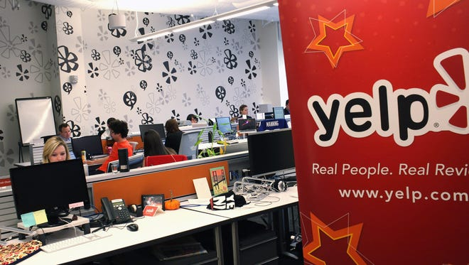 Employees of the online review site Yelp watch as New York City Mayor Michael Bloomberg speaks at the new East Coast headquarters of the tech company in New York City.