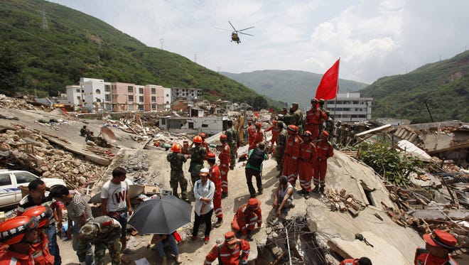 Rescuers stand over the debris of collapsed houses following an earthquake in Longtoushan township of Ludian county in Zhaotong, southwest China on Tuesday.