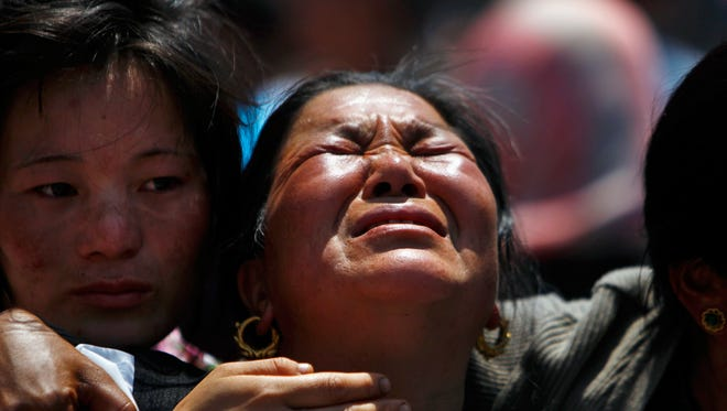 Relatives of mountaineers, killed in an avalanche on Mount Everest, cry during the funeral ceremony in Katmandu, Nepal, on April 21, 2014. Buddhist monks cremated the remains of Sherpa guides who were buried in the deadliest avalanche ever recorded on Mount Everest, a disaster that has prompted calls for a climbing boycott by Nepal's ethnic Sherpa community.