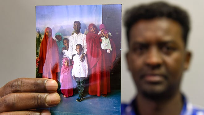 Abdikarim Osman Omar holds a photo of his wife and children stuck in Kenya Friday, July 6, because of the national travel ban.