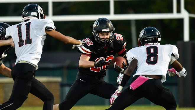 Harding defenders Dejaun Smith and T.J. Jefferson converge on Pleasant running back Clay Cheney on Friday night. The Presidents' defense bottled up Pleasant for 87 total yards in the first half en route to a 41-21 Mid Ohio Athletic Conference Red Division victory.