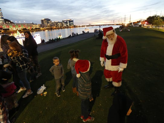 Santa greets children on the shore prior to the Fantasy