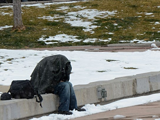 A homeless man covers himself with a jacket as snow
