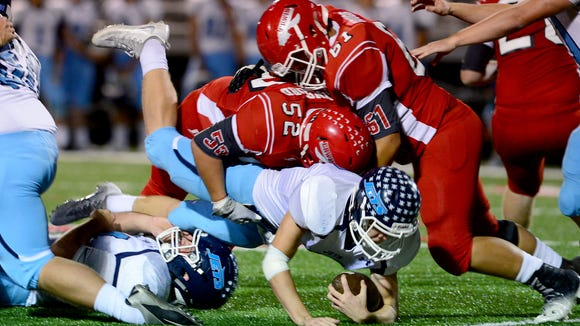 Enka quarterback Avery Holbrook gets taken down by Erwin's Ethan Lunsford and Jackson Gouge during a 2016 game.