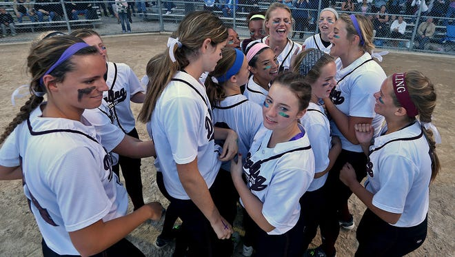 Dowling Catholic players celebrated at home plate after their 8-1  win over Ankeny Centennial in 5-A regional final softball game at Dowling Catholic High School in West Des Moines on Tuesday night July 15, 2014.
