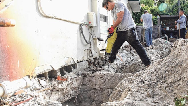 Josh May, of NSquare Inc., uses a jackhammer to break up old concrete under the foundation of a home in San Carlos Park on Tuesday.