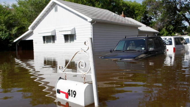 A home and three vehicles are surrounded by the Souris River flood waters in the Minot, N.D., neighborhood of Oak Park on June 25, 2011.