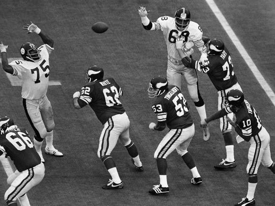 Pittsburgh Steelers tackle Joe Greene (75) gets ready to block a pass as Minnesota Viking players Andy Maurer (66), Ed White (62), Mick Tingelhoff (53) and Ron Yary (73) protect quarterback Fran Tarkenton (10) during Super Bowl IX at Tulane Stadium in New Orleans. Tingelhoff will be inducted into the Pro Football Hall of Fame on Saturday.