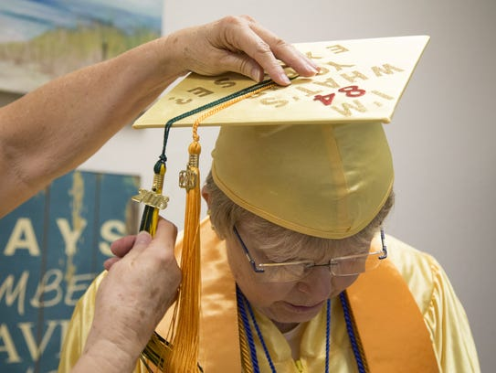 Gwendolyn Carlson, 84, gets dressed in her cap and